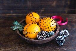 Orange and clove pomanders in wooden bowl (festive)