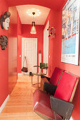 Old cinema chair in red hallway with fitted cabinets and white door