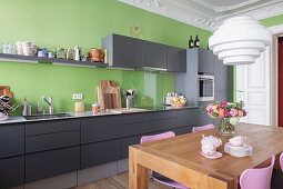 Dining table in kitchen with grey cabinets, green wall and stucco ceiling
