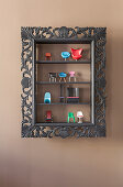 Miniature designer chairs in display cabinet with black frame
