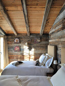 Twin beds in rustic bedroom with wooden walls