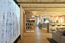 Wooden ceiling and open-plan kitchen in large, open-plan interior