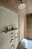 Rainfall shower in front of concrete shower wall in wood-clad bathroom