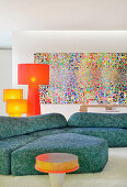 Blue sofa and colourful artwork in artistic living room