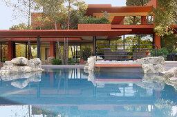 Pool vor einem roten Architektenhaus mit mehreren Ebenen