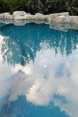 Blauer Himmel und Wolken spiegeln sich im Pool mit Steinbegrenzung
