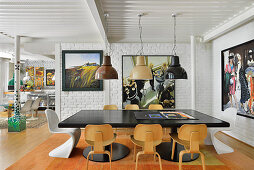 Black dining table and classic chairs in front of white-painted brick wall in open-plan living area