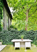Stone table and chairs in front of hedge on terrace