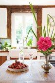 Erdbeeren, Wasserkaraffe und Zinnvase mit Pfingstrose auf Küchentisch