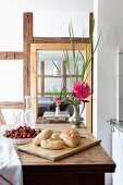 Bread rolls on chopping board, strawberries and peony on wooden table