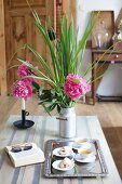 Pastries and tea on tray next to book and pink peonies on table