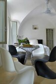 Black and white Panton chairs at round table with glass top in period interior