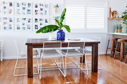 Rustic wooden table with white metal chairs, photo gallery next to the window in the open kitchen