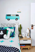 Boy's room with bed, bedside table and car motif on the wall