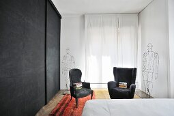 Black cupboards and two armchairs next to wire sculpture in bedroom