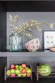Flowering twigs and fruit in metal baskets on grey kitchen shelves