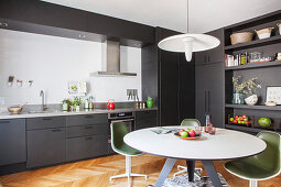Round dining table and retro chairs on zebra-skin rug in grey fitted kitchen