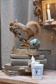 Still-life arrangement with stuffed squirrel on stack of vintage books