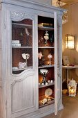 Various ornaments in antique wooden cupboard in vintage-style interior