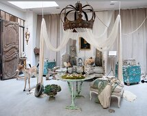 Collection of antiques and stuffed animals below canopy and antique metal crown