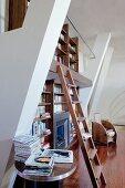 Bücherwand auf zwei Etagen mit einer Holzleiter