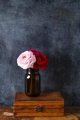 Jar of ranunculus on wooden box against black wall