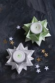 Aus grünem und weißem Papier gefaltete Sterne als Teelichthalter