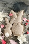 Two fabric rabbits with zig-zag edge and paper flowers