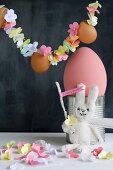 Fabric rabbit below garland of threaded paper flowers and eggs