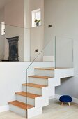 Staircase with glass balustrade in interior with traditional fireplace