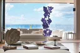 Vertical flower arrangement in living room with view of sea through panoramic window