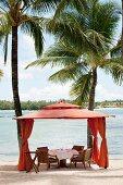 Elegant dining area in orange fabric pavilion under palm trees on beach