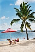 Palm tree, next to table and two chairs below red parasol on idyllic white beach