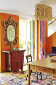 Baroque mirror and Chinese cabinet against orange wall and coconut fibre lamp above dining table