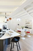 Round dining table and designer chairs in open-plan kitchen with wood-beamed ceiling