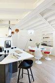 Runder Esstisch und Designerstühle in der offenen Küche mit Balkendecke