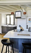 Bar stools at counter in quirky kitchen with odd angles
