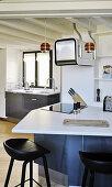 Verwinkelte Küche mit Barhockern vor der Küchentheke
