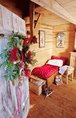 View of small bed in wooden Alpine cabin seen through open front door with wreath