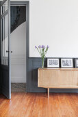 Black and white photos and flowers on sideboard against dove grey wainscoting