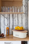 Bread box, vegetables and glasses on shelf against tree-patterned wallpaper