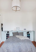 Double bed with polka-dot bed linen in bedroom