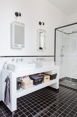 Twin sinks on washstand and shower cubicle in black and white bathroom