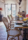 Tables set for breakfast and vintage cane chairs in dining room