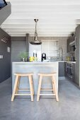 Stools at breakfast bar in kitchen in shades of grey