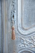Key with tassel in artistically carved, antique wooden door