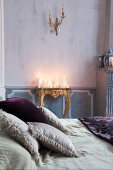 Arrangement of white candles of various shapes on antique gilt console table with scatter cushions on double bed in foreground