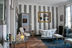 White, free-standing bathtub, gilt picture frame, ornaments and striped walls in cosy bathroom