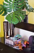 Gifts wrapped in colourful paper and lot tealights on black sideboard next to vase of green artificial leaves