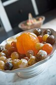 Candied fruits in white china dish on marble surface